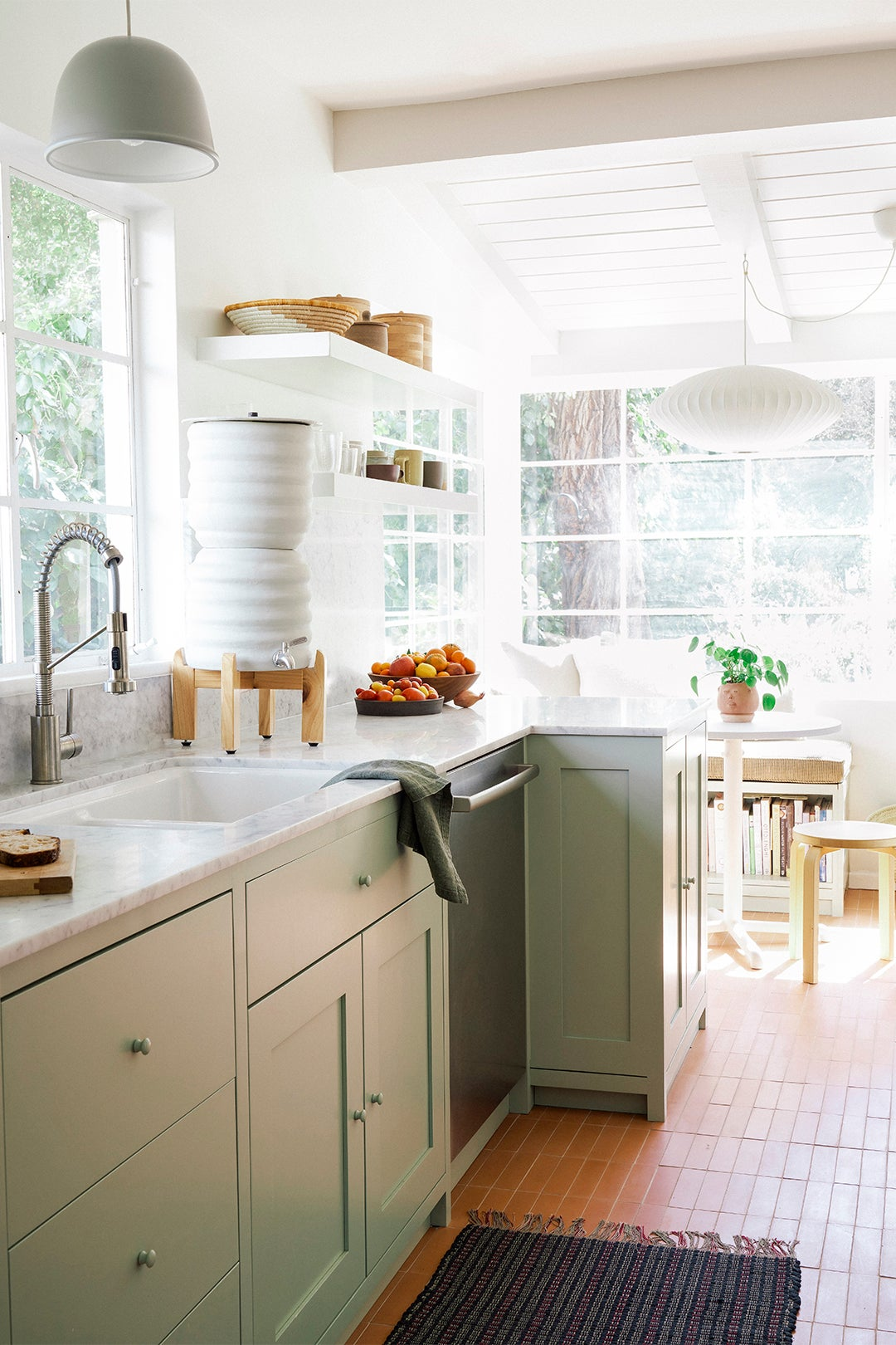 green lower cabinets in a bright kitchen