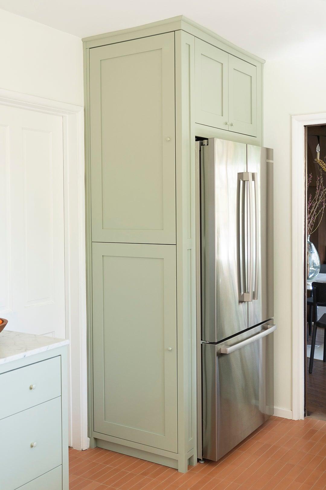 fridge inset into green cabinets