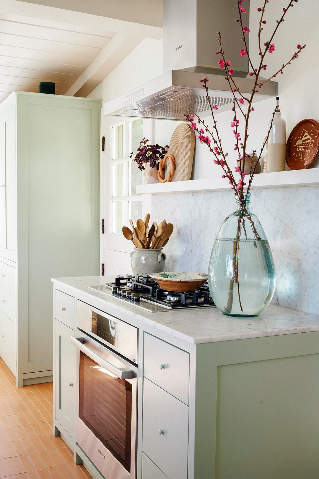 green lower cabinets around a stove