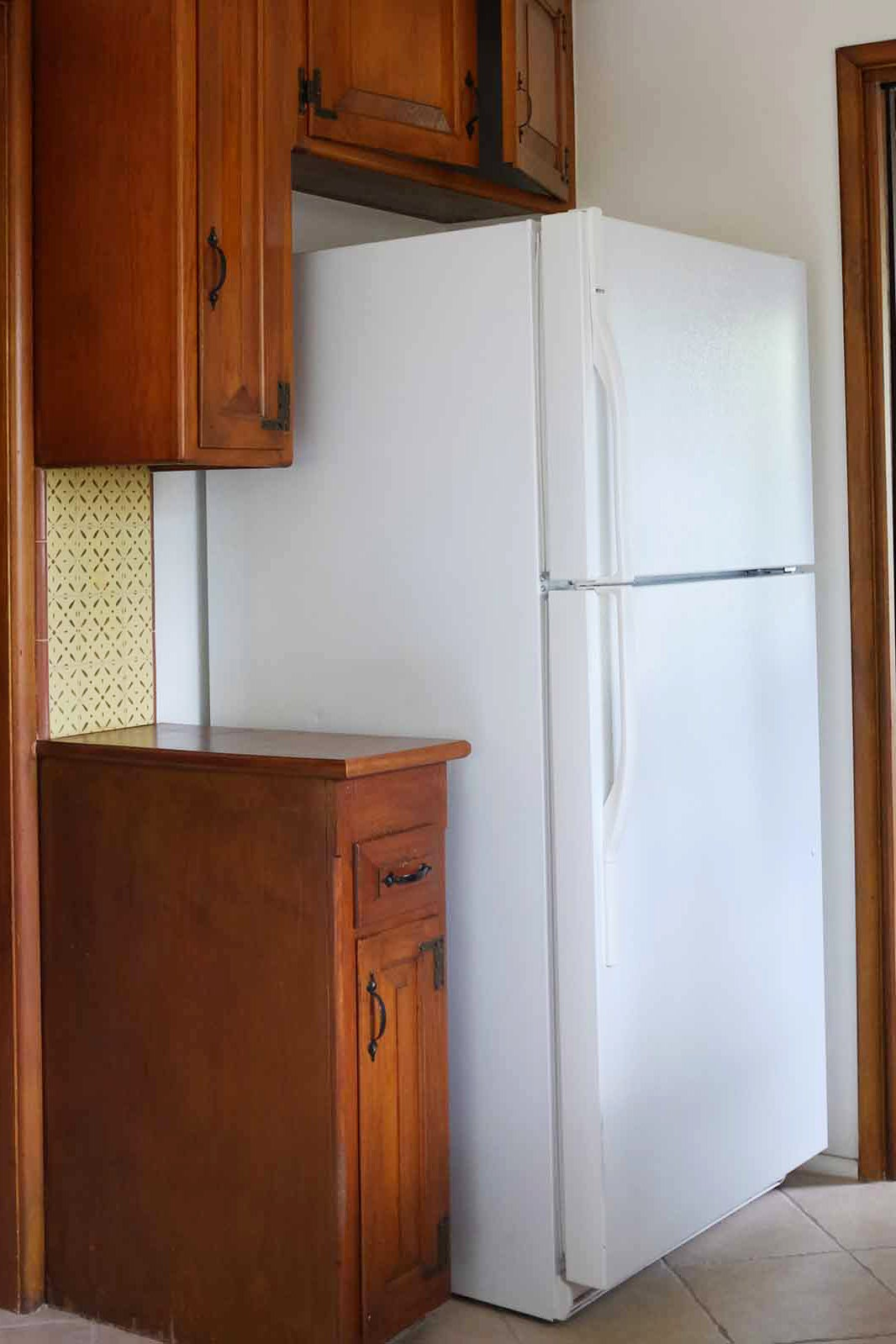 white fridge with dated wood cabinets