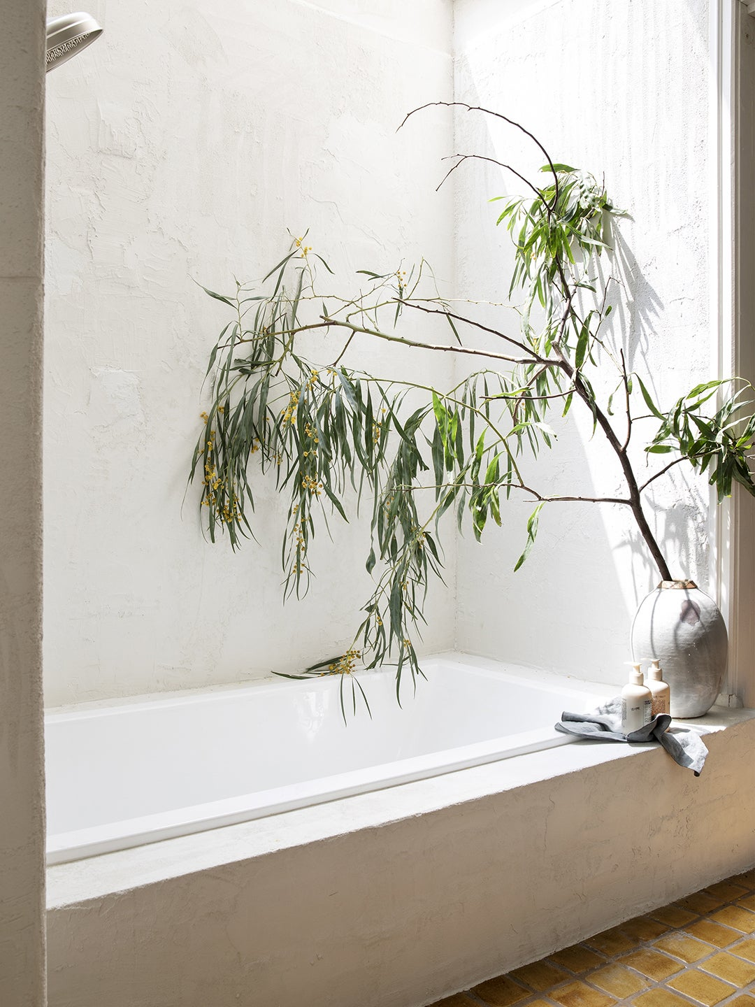 white shower walls with large branch in a vase