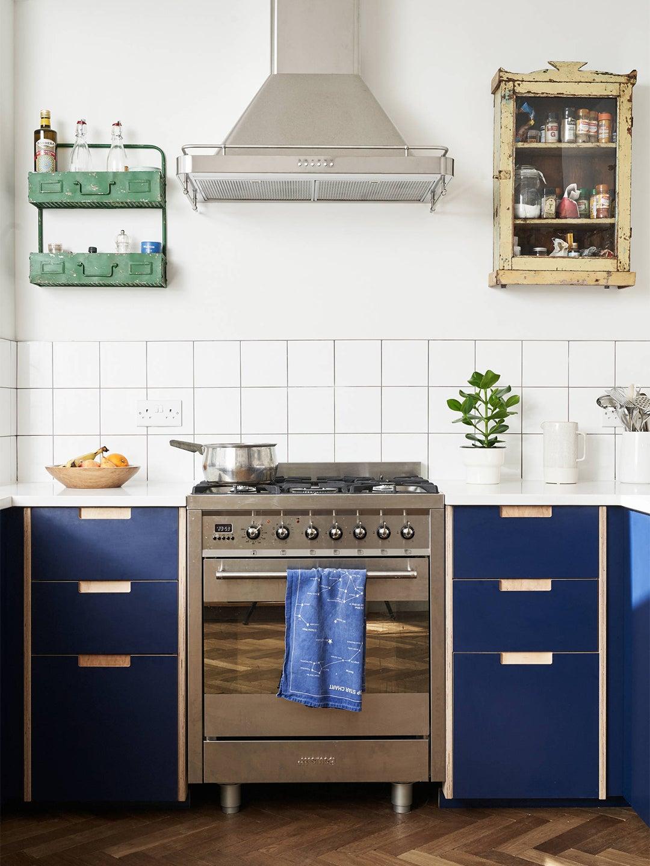 blue kitchen with white backsplash tiles