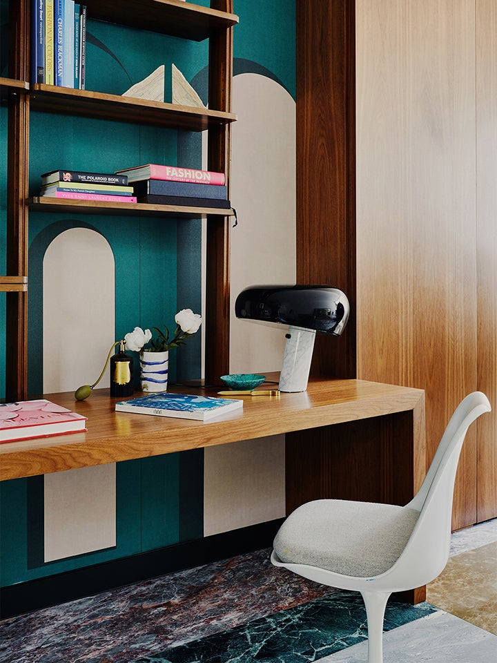 turquiose wall with white chair and wood desk