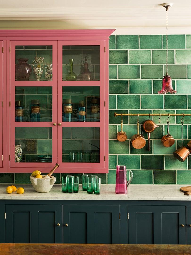 pink glass front kitchen cabinet against green tile backsplash