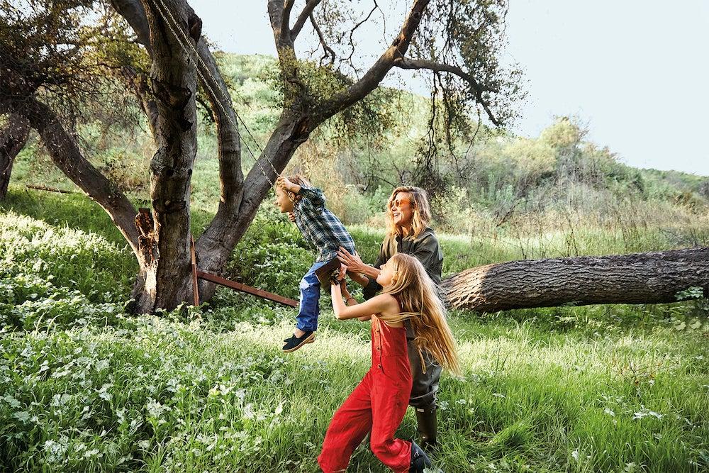 woman pushing child on swing