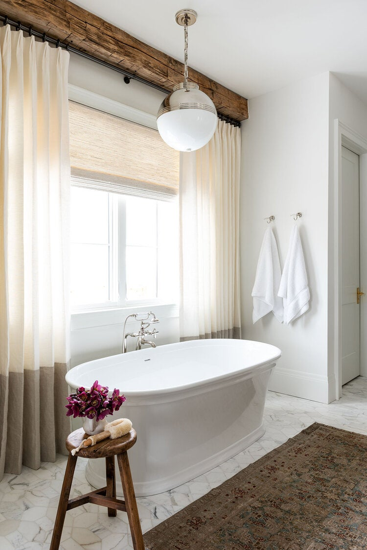 bathtub in front of curtains and rustic wood beam