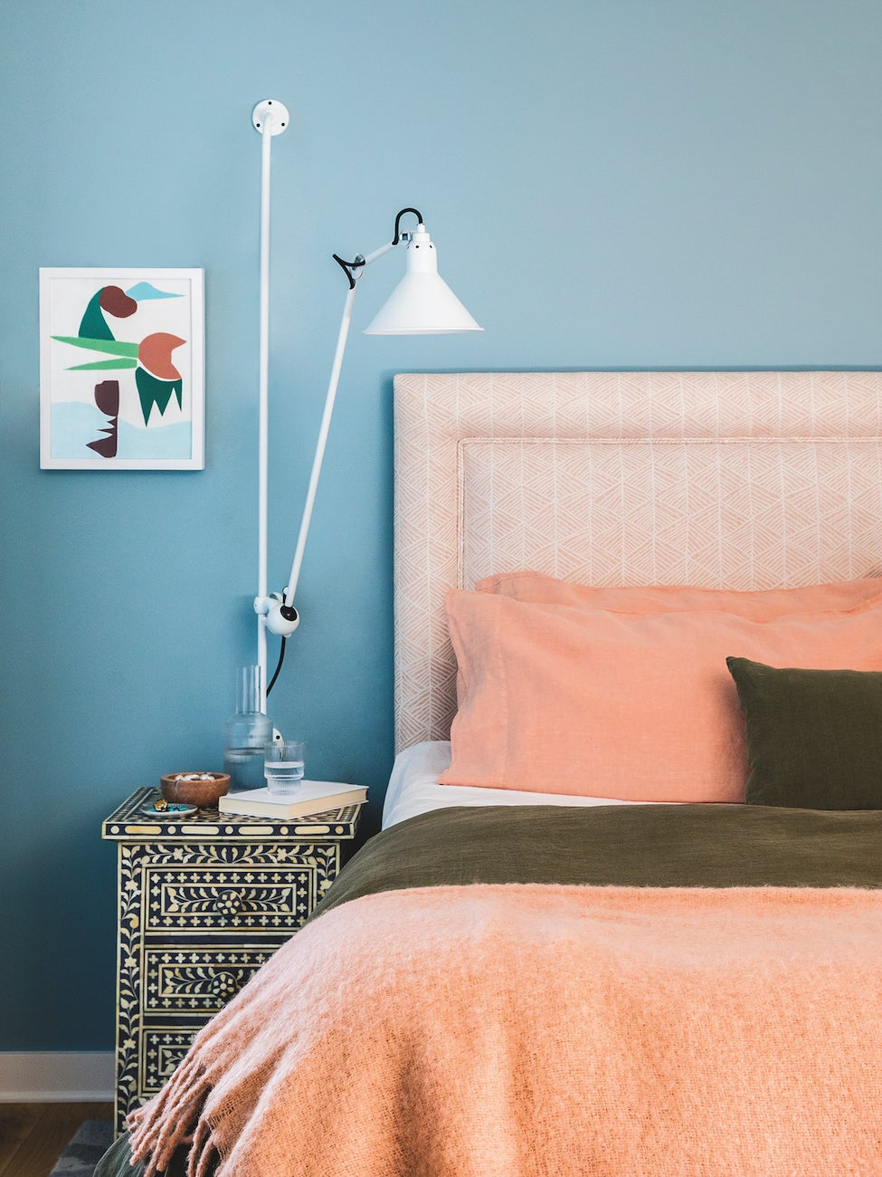 Bedroom with blue walls and peach sheets