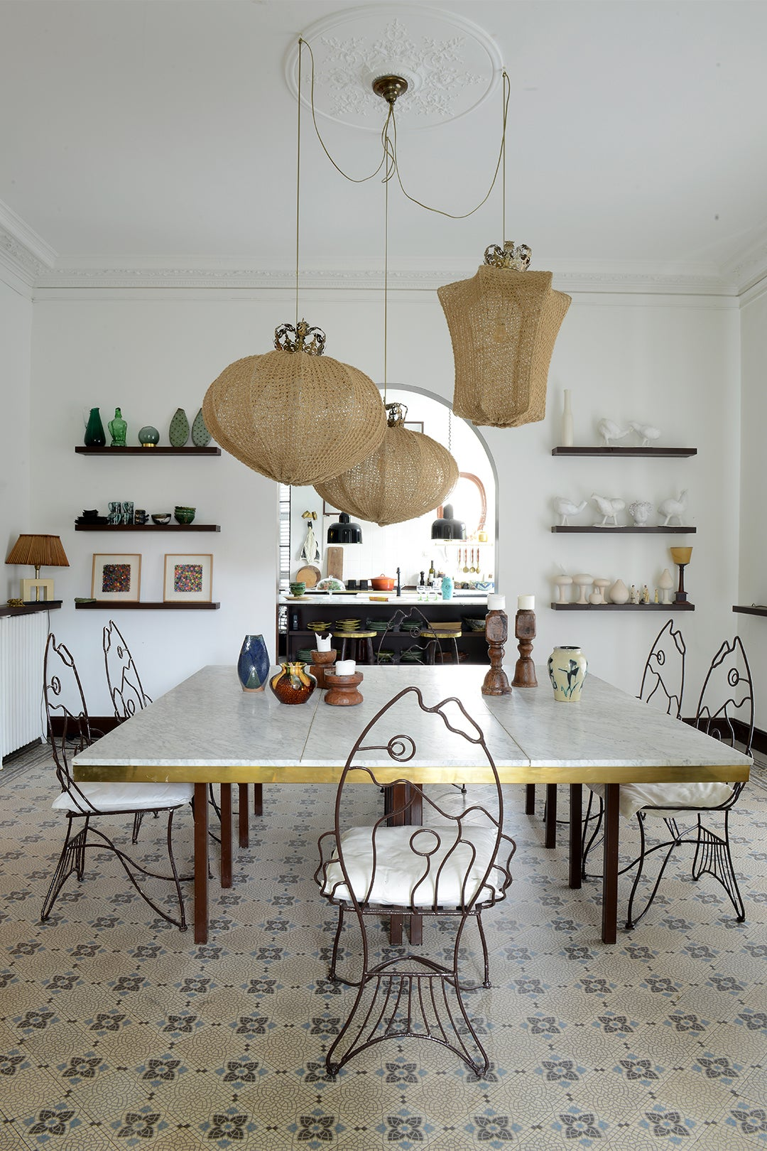 dining room table with fish shaped chairs and three woven pendants