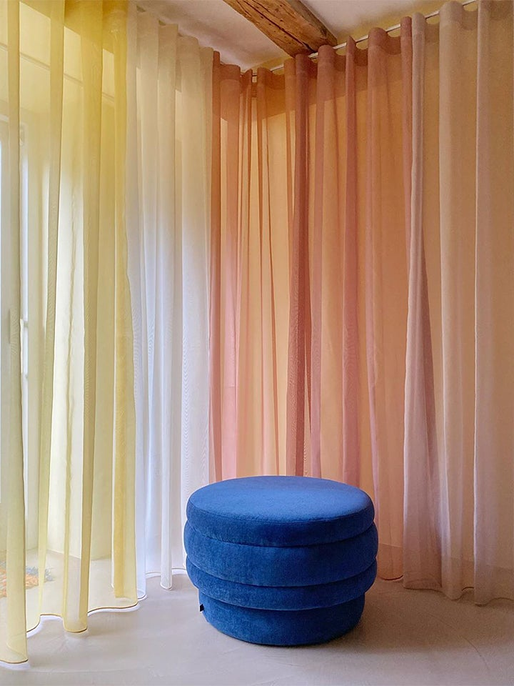 rainbow colored curtains and Klein blue stool