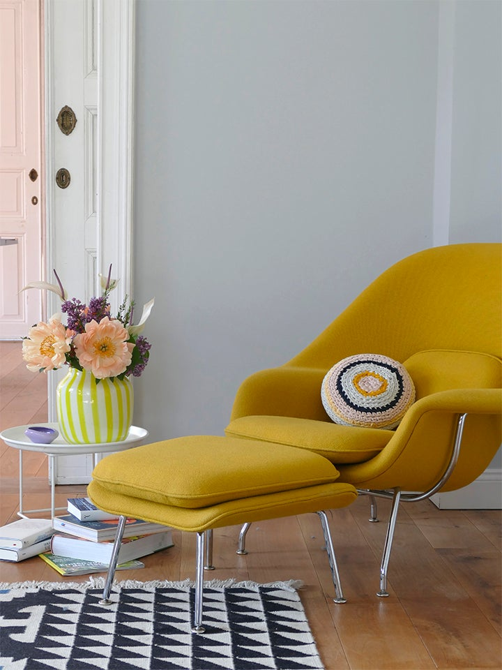 blue wall behind yellow armchair