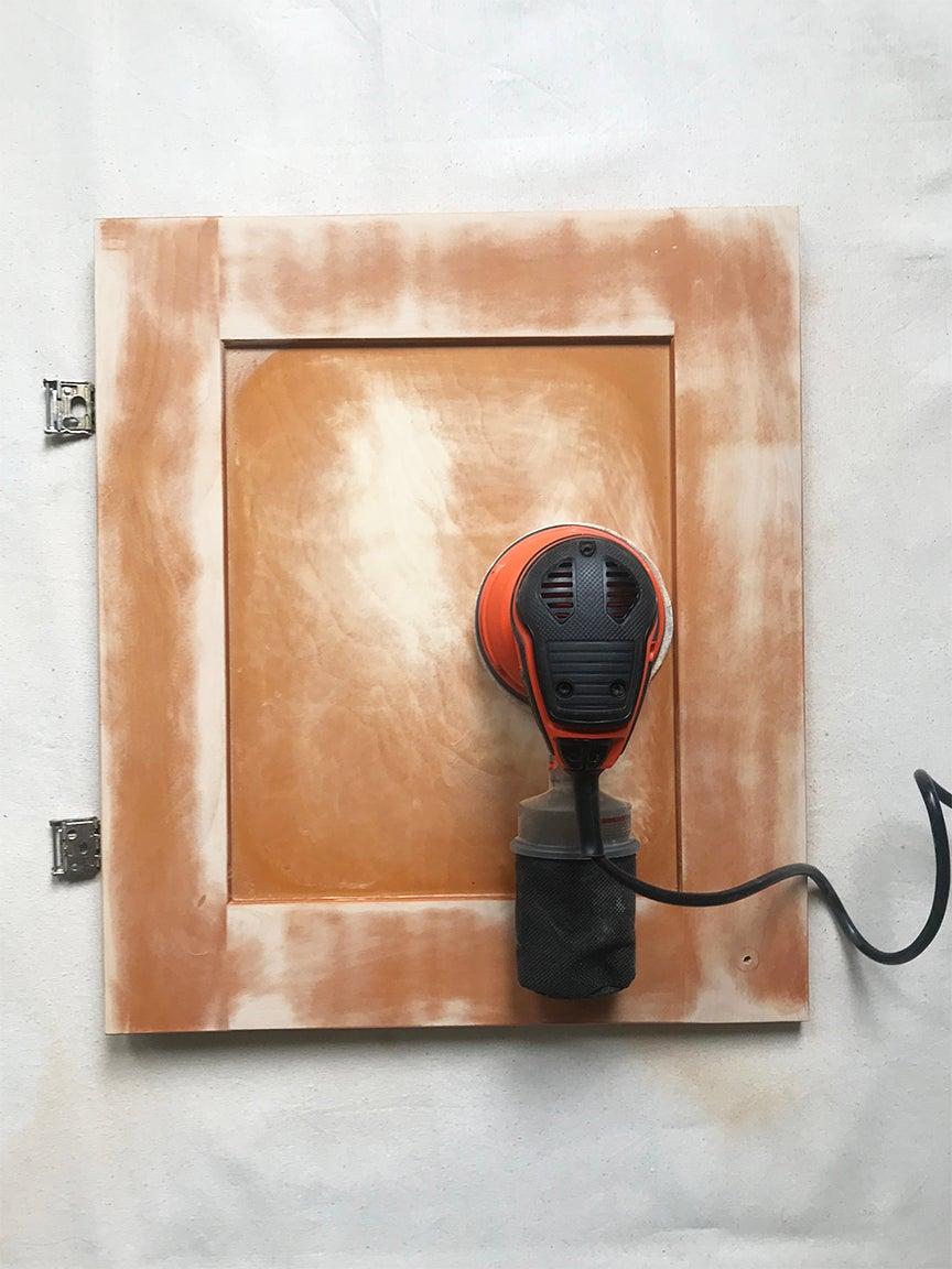 Cabinet door being sanded