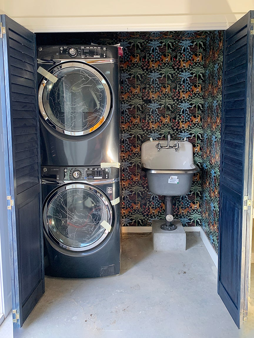 laundry closet with two machines and grey sink