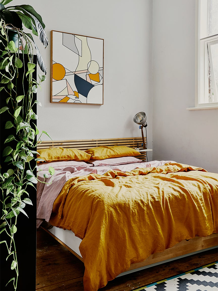 Bedroom with low bed and yellow sheets