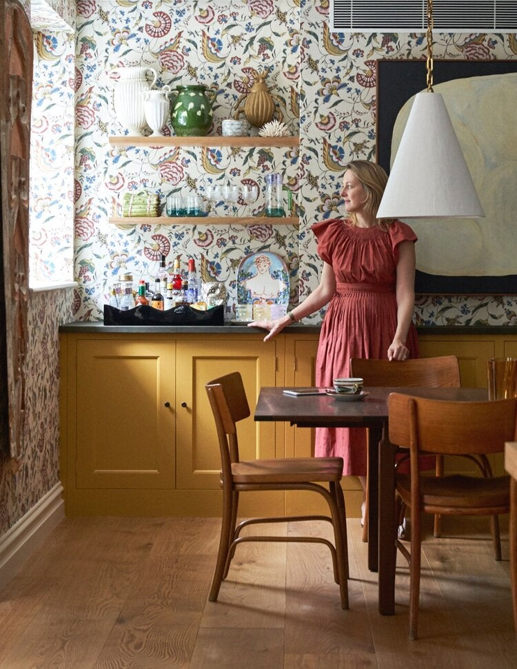 Rita Konig in a kitchen with mustard colored cabinets