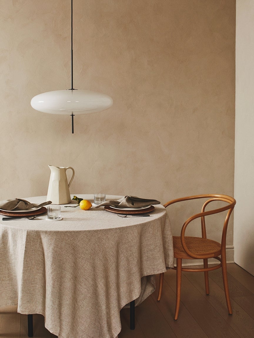 neutral table setting with pendant light and wooden chair