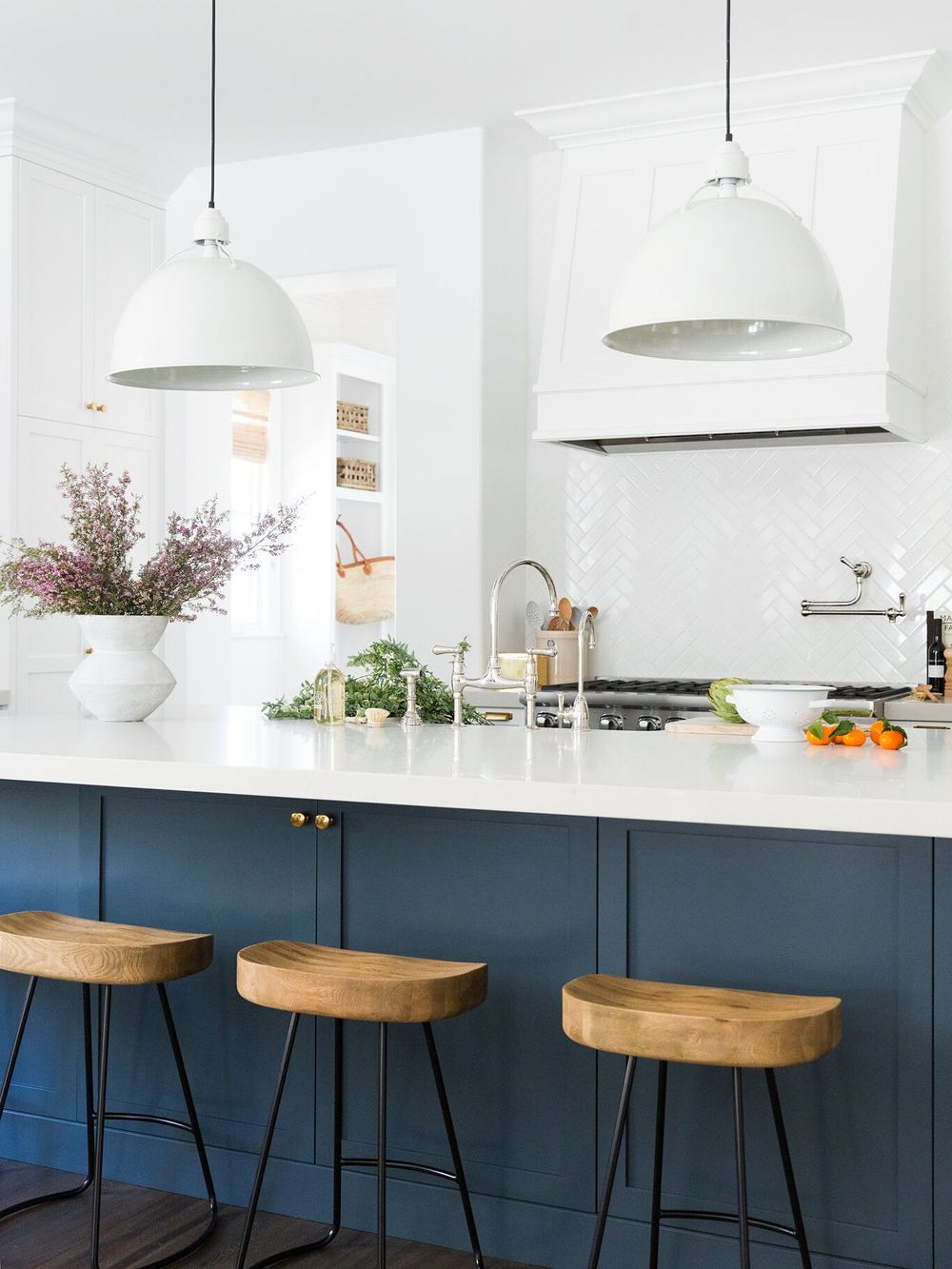 white and blue kitchen with bar stools at island