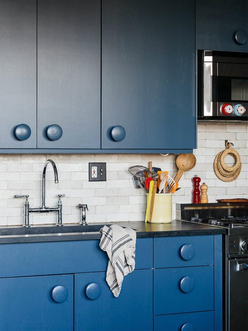blue kitchen cabinets with big round knobs