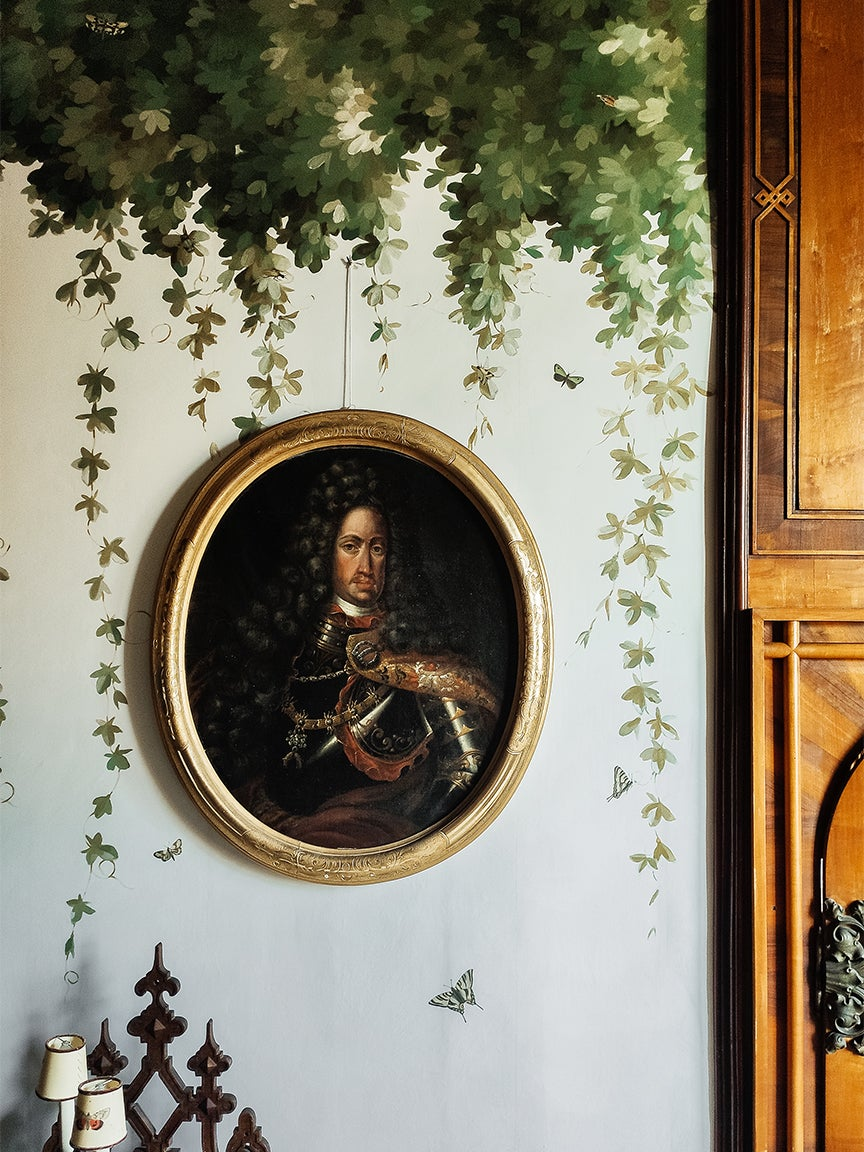 vintage oil portrait hanging on wallpapered wall