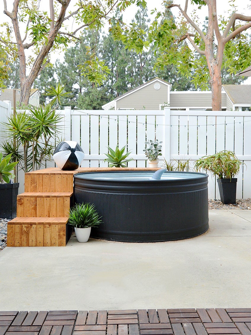 black stock tank pool with wood deck