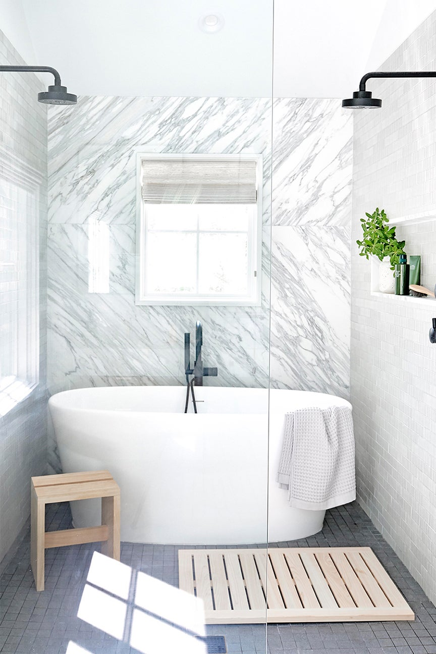 marble bathroom with grey floor tiles and big white tub