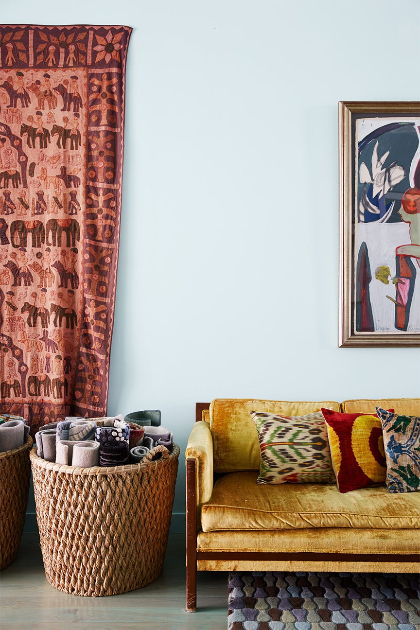 Yellow velvet sofa with colorful pillows