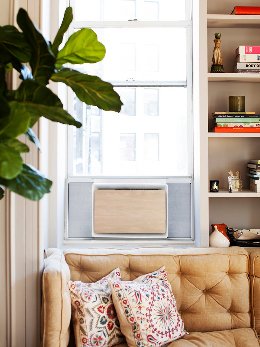 living room corner with window AC unit next to bookcase