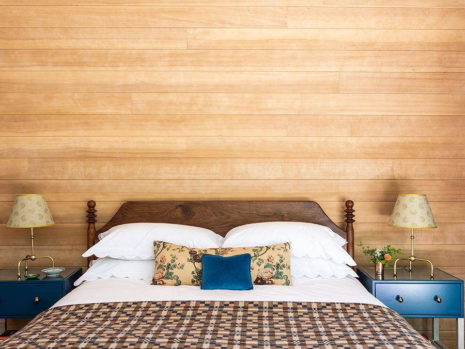 Bedroom with wood-paneled walls