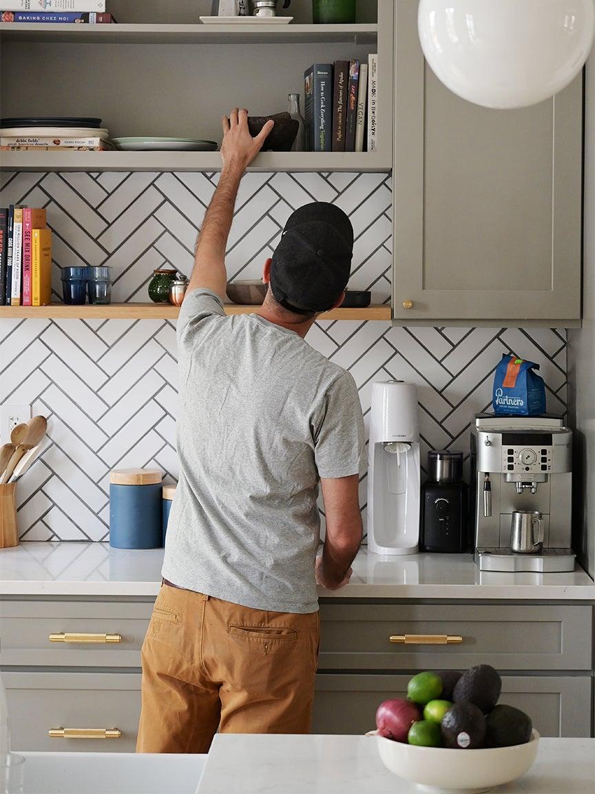 Kitchen with gray cabinets and herringbone backsplash