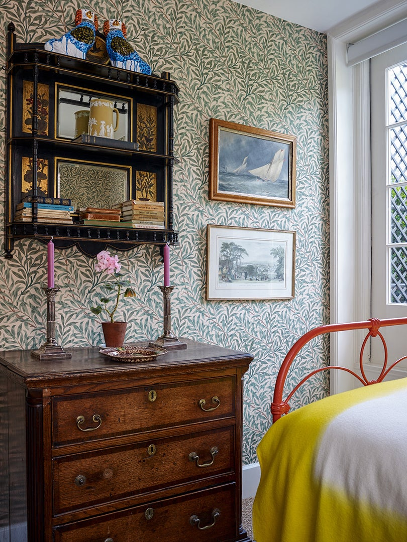 Bedroom with leafy wallpaper and red bed frame