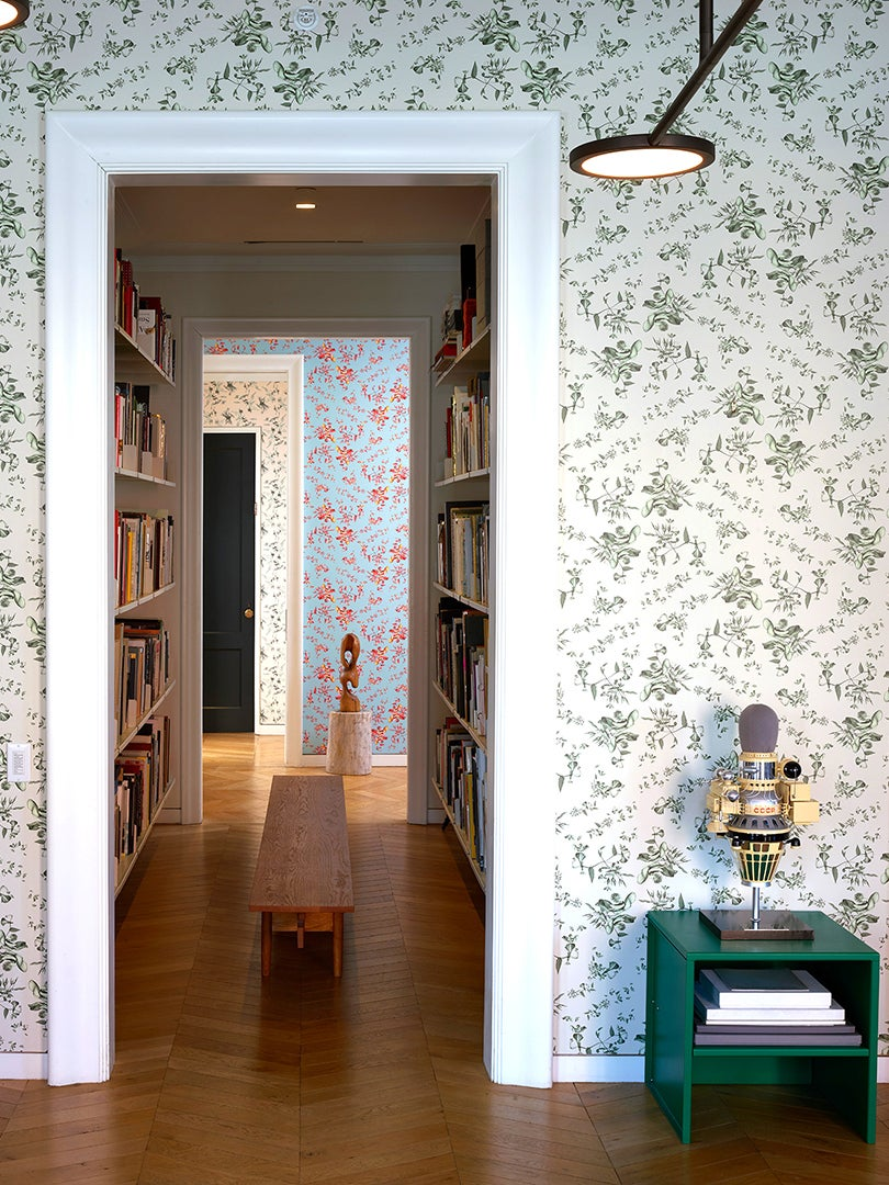 Room with leafy wallpaper and library hallway