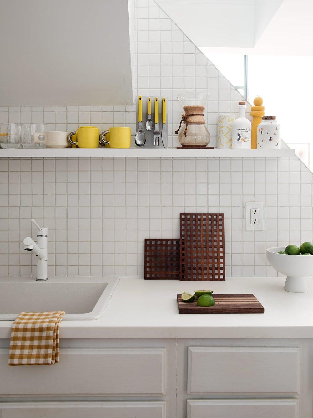 White kitchen counter with white shelf above