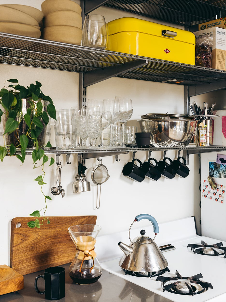 Small apartment kitchen with shelving above stove