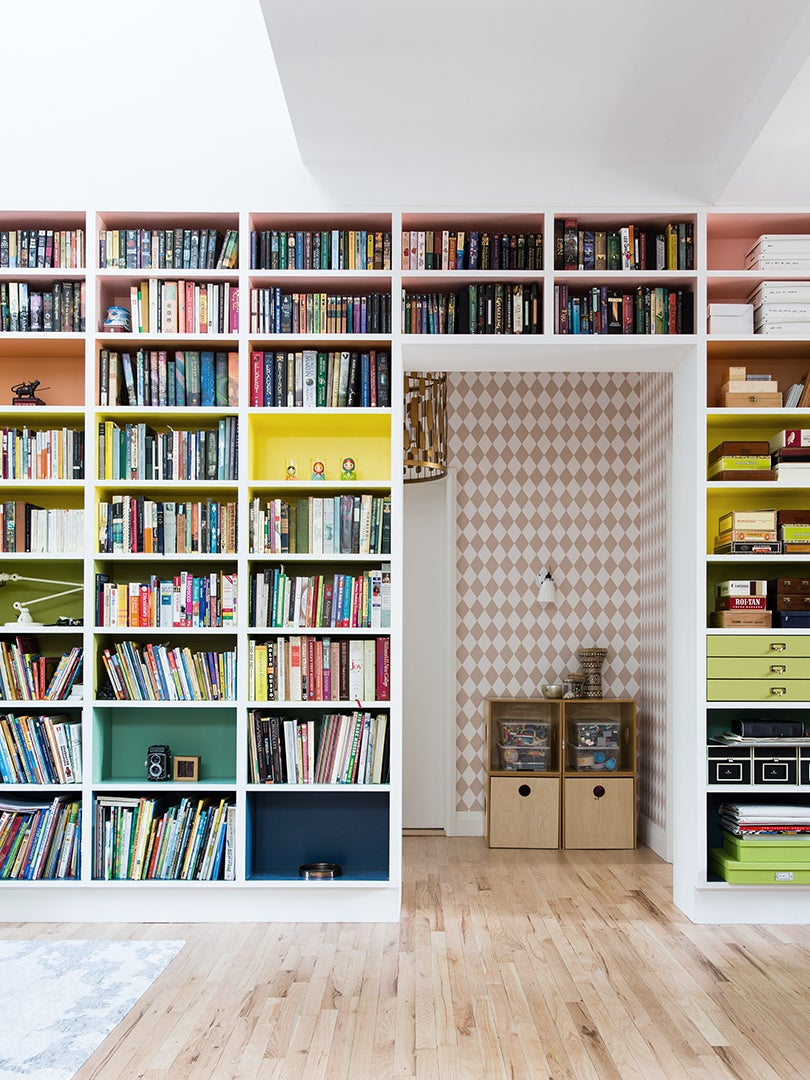 wall of built in bookshelves with rainbow colored backings