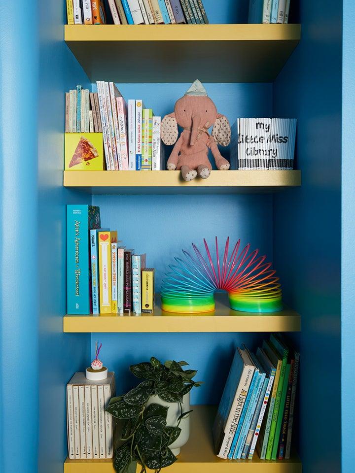 blue and yellow bookshelf for nursery