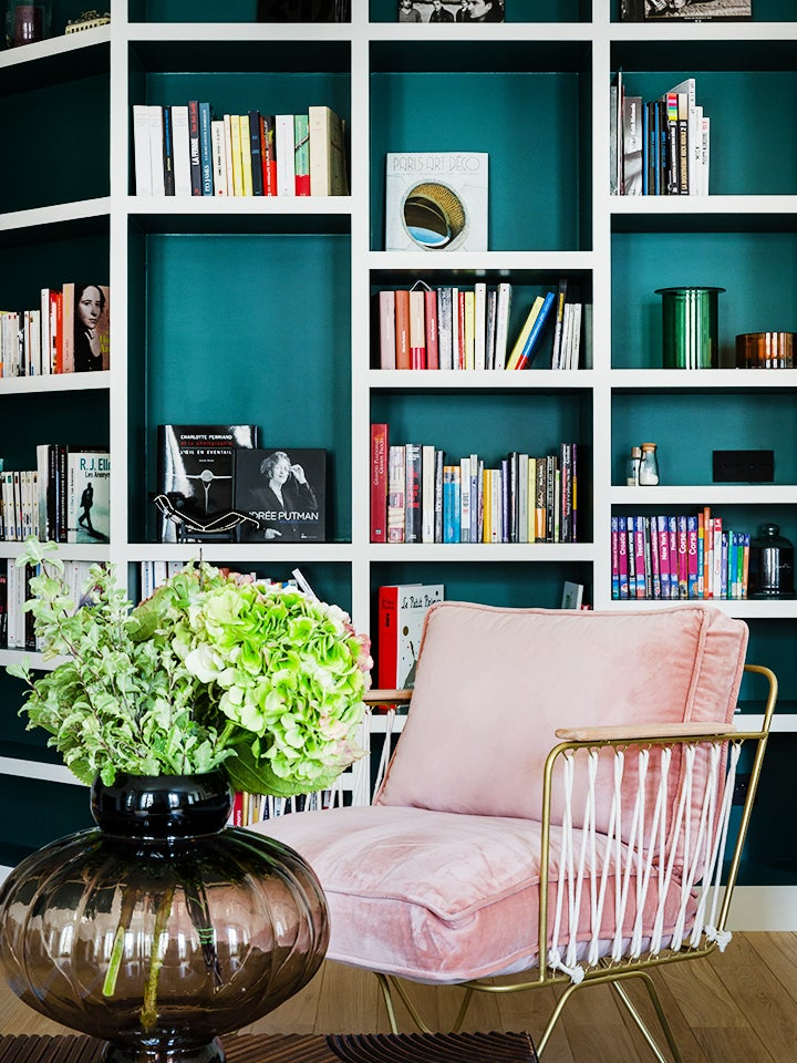 green and white bookcase behind pink armchair