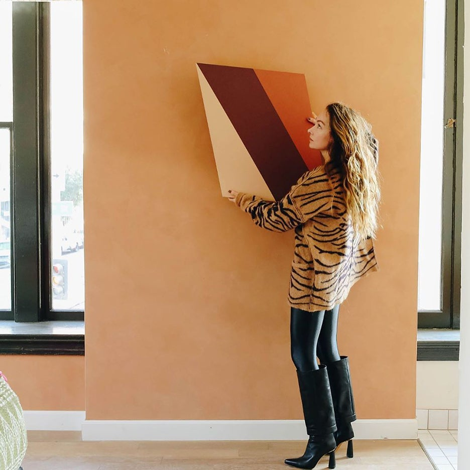 woman holding up a painting