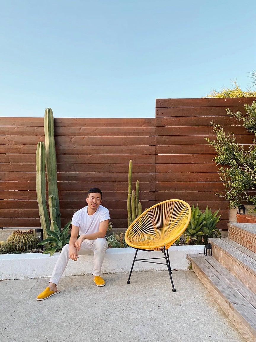 man sitting on wall near garden