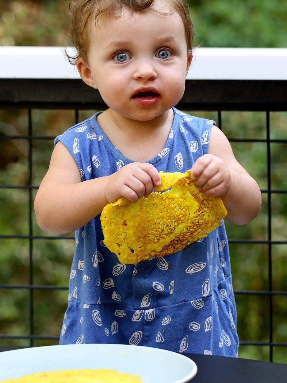 baby in blue dress holding dosa pancake