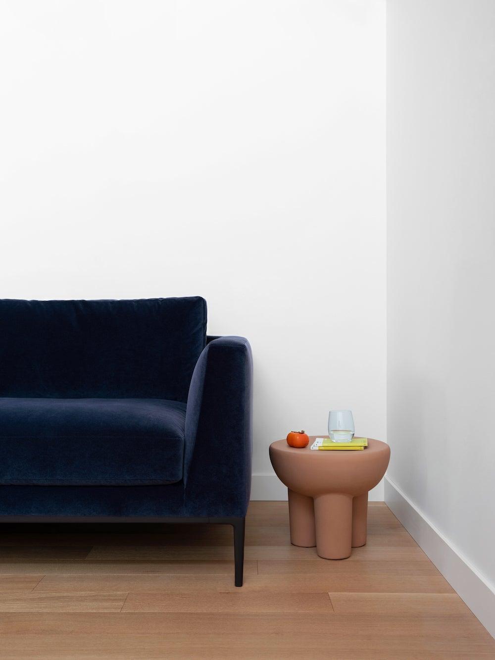 blue sofa next to terracotta stool