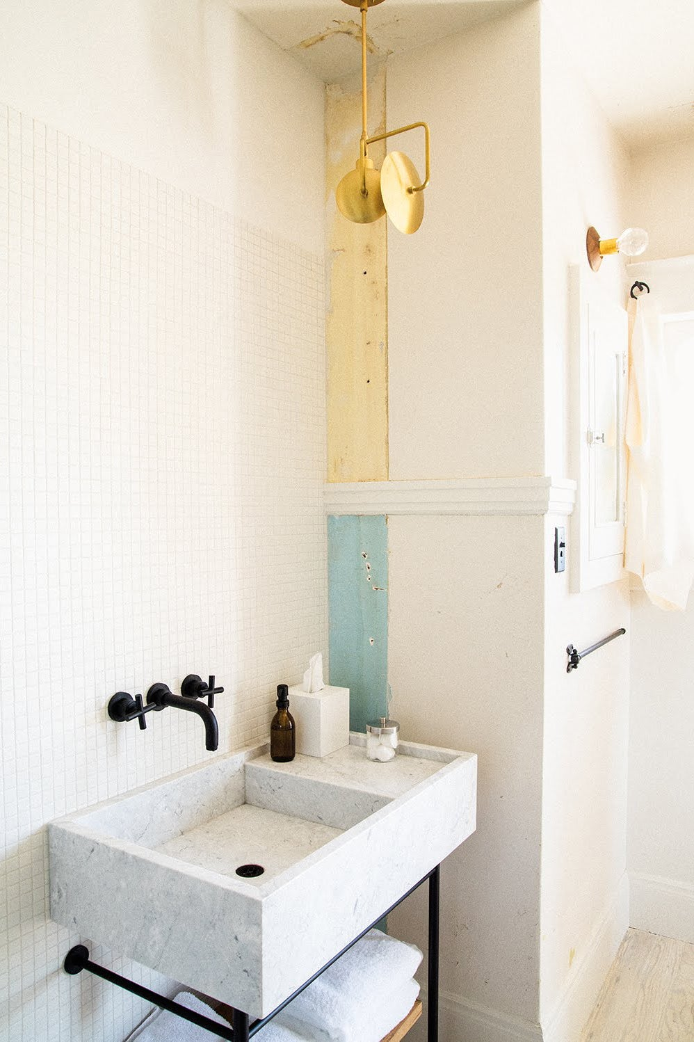 white tile bathroom with gold pendant