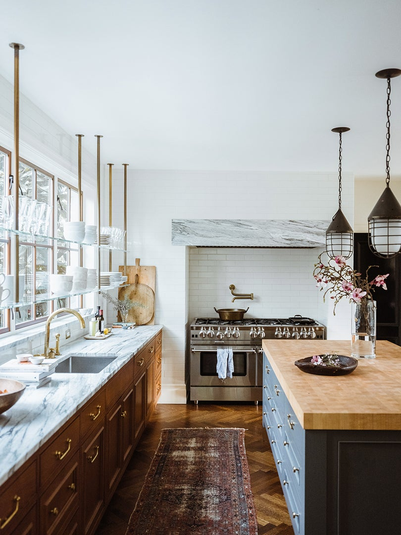 large kitchen with open shelving across windows