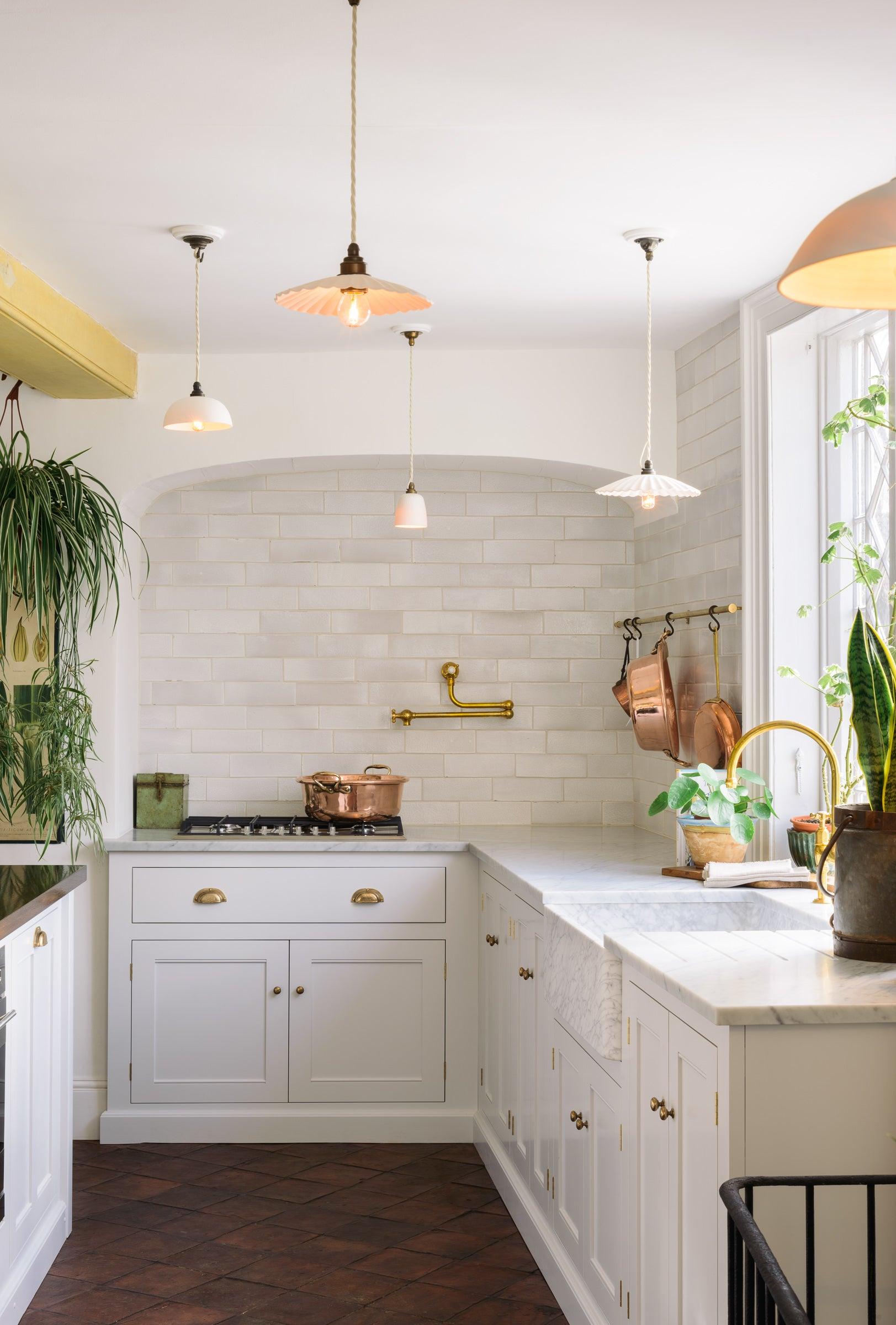 White kitchen with terracotta floors