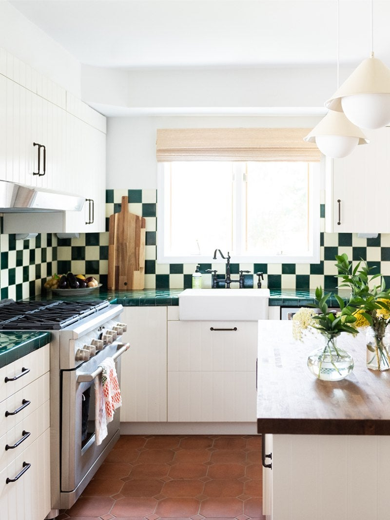 Kitchen with green-and-white backsplash and terracotta floors