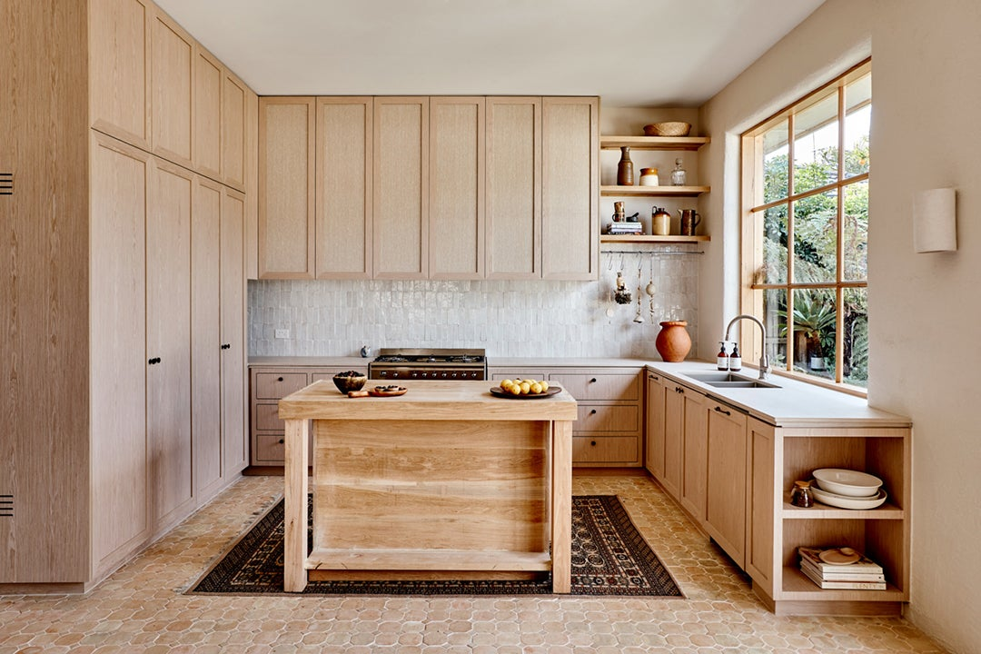 Pale wood kitchen with terracotta floors