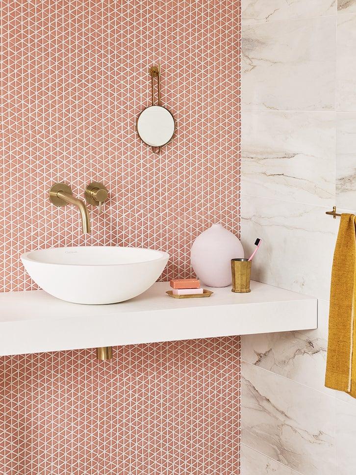 coral mosaic bathroom tile backsplash with white sink