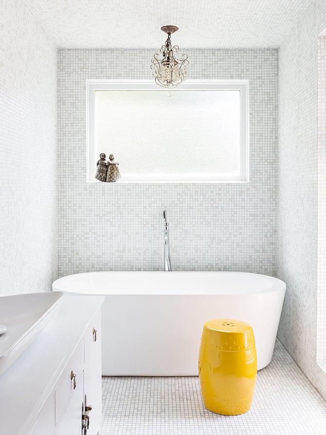 white tile bathroom with yellow stool
