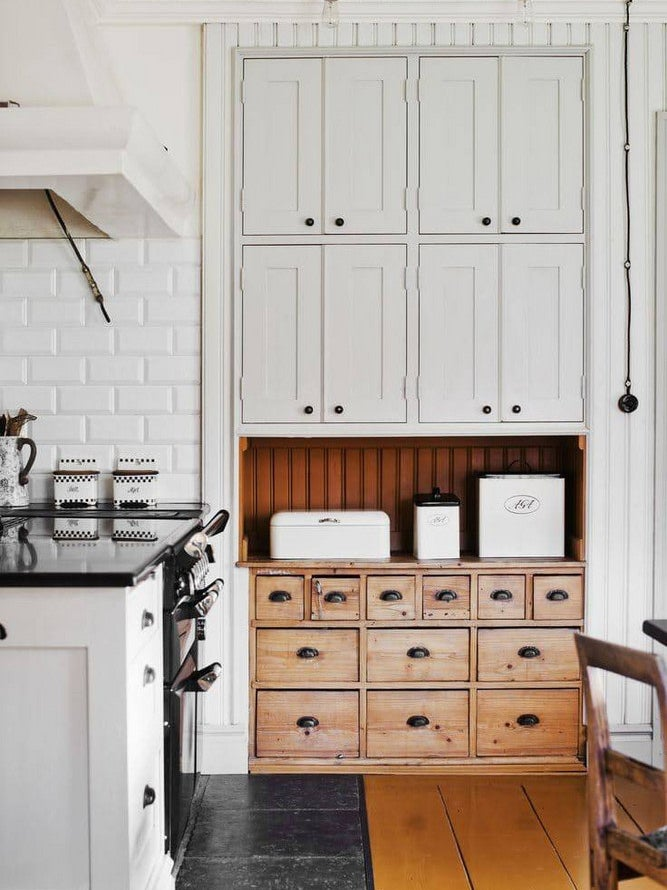 white kitchen with built in antique drawers