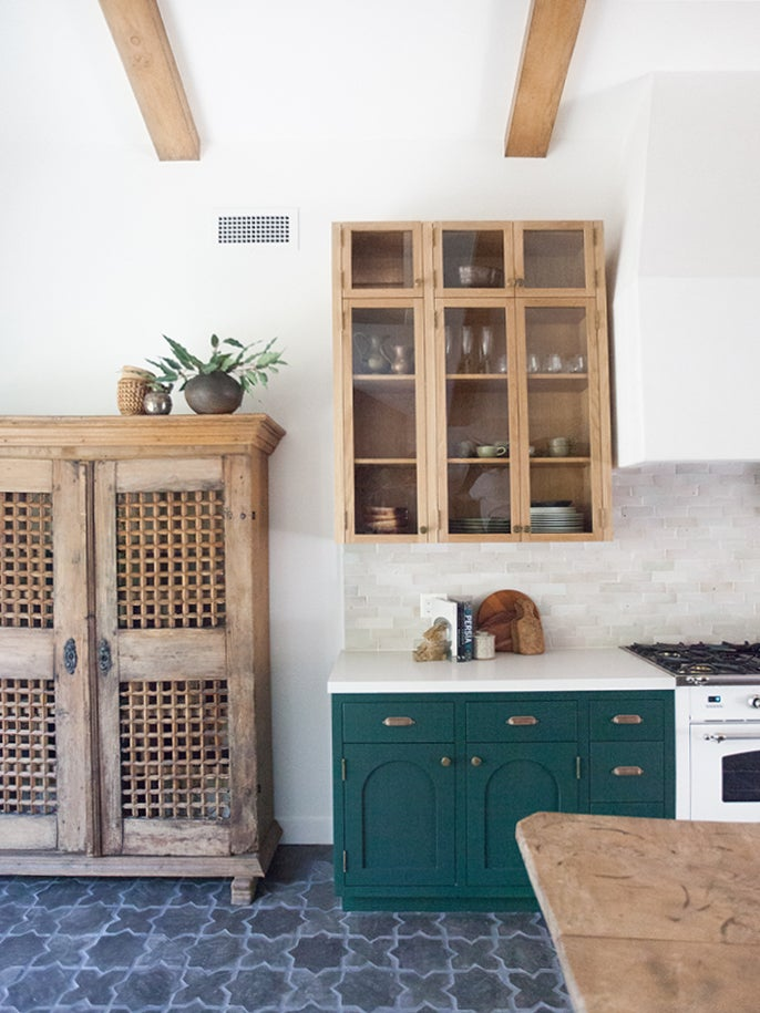 white rustic kitchen with antique wood cabinets and green cupboards