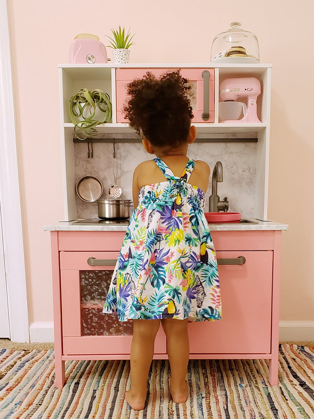 Toddler in front of pink play kitchen