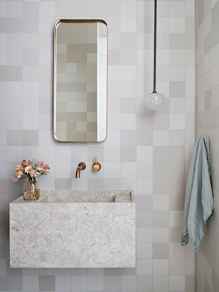 grey tile bathroom with rectangular mirror